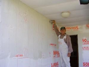 οικοδόμος εφαρμόζει επιληπτικό πάνω σε τοίχο που γίνεται θερμοπροσοψη